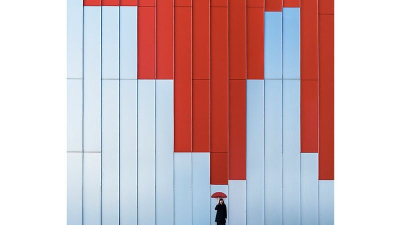 A woman with a red umbrella stands in front of a tall red and blue wall five times taller than her. Photo by Daniel Rueda and Anna Devís.